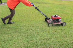 Worker cutting green grass field by engine lawn mover Royalty Free Stock Photos