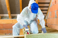 Worker cutting insulating material Royalty Free Stock Image
