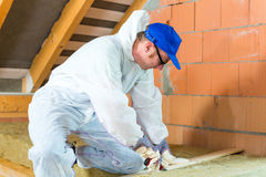 Worker cutting insulating material Stock Image