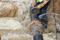 Worker cutting iron pipe Royalty Free Stock Photography