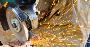 Worker cutting metal with grinder Stock Photos
