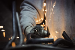 Worker cutting metal with grinder. Sparks flying while grinding. Stock Image