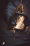 Worker cutting metal with grinder. Sparks flying while grinding. Royalty Free Stock Photo