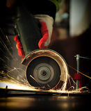 Worker cutting metal with grinder. Sparks while grinding iron Royalty Free Stock Photography