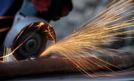 Worker cutting metal with grinder Stock Image