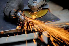 Worker cutting metal with grinder Stock Photography