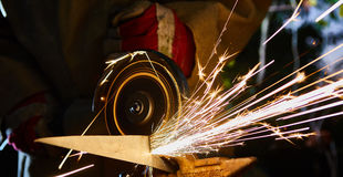 Worker cutting metal with grinder. Sparks while grinding iron Stock Photos