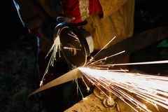 Worker cutting metal with grinder. Sparks while grinding iron Royalty Free Stock Photos