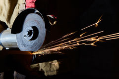 Worker cutting metal with grinder. Sparks while grinding iron Stock Photography