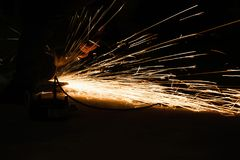 Worker cutting metal with grinder, sparks while grinding iron. Low key photography. Space for text Royalty Free Stock Photo
