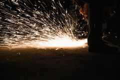 Worker cutting metal with grinder, sparks while grinding iron. Low key photography. Space for text Stock Photos