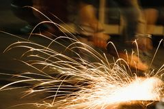 Worker cutting metal with grinder, sparks while grinding iron. Low key photography. Space for text Royalty Free Stock Image