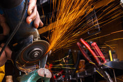 Worker cutting metal with grinder. Sparks while grinding iron. S Royalty Free Stock Photo