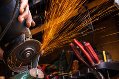 Worker cutting metal with grinder. Sparks while grinding iron. S. Elective low focus Stock Photos