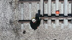 Railroad worker repairing a broken track. Working metal. Worker cutting metal rail tracks.