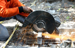 Worker cutting metal  with saw disk. Industrial worker cutting metal  with saw disk Stock Photo