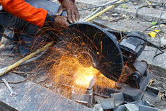 Worker cutting metal  with saw disk. Industrial worker cutting metal  with saw disk Royalty Free Stock Images