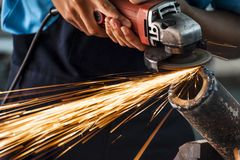 Grinding machine. Worker cutting metal using grinding machine Stock Images