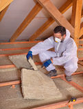 Worker cutting mineral wool panel to install thermal insulation Stock Photos