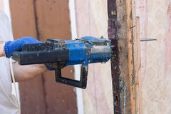 Worker cutting old beam using a chainsaw close up. Stock Images