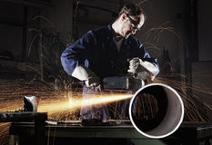 Worker cutting pipe with angle grinder. Heavy industry worker cutting steel pipe with angle grinder in workshop Royalty Free Stock Photos