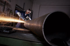 Worker cutting pipe with angle grinder. Heavy industry worker cutting steel pipe with angle grinder in workshop Royalty Free Stock Image