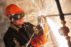 Worker cutting pipe with sparks by grinder flame torch cutter Royalty Free Stock Photos