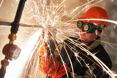 Worker cutting pipe with sparks by grinder flame torch cutter Royalty Free Stock Photo
