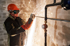 Worker cutting pipe with sparks by grinder flame torch cutter Stock Photography