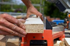 Worker Cutting Plywood Using Circular Saw. Industrial Concept. stock photography