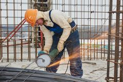 Worker cutting rebar by grinding machine Stock Photo