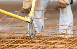 Worker cutting reinforcement mesh. Close up of pliers cutting reinforcement mesh at building site Royalty Free Stock Images