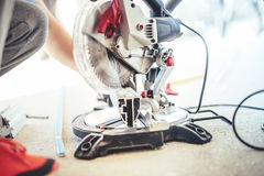 worker cutting and sawing metal with circular grinder, mitre-saw Royalty Free Stock Photos