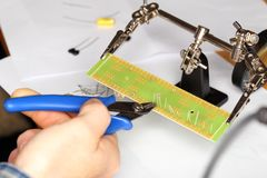 Worker is cutting some electronics. Worker is cutting some electronic elements on a board stock photo