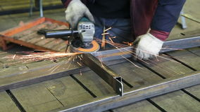 Worker cutting steel with angle grinder. Construction worker using an angle grinder producing a lot of sparks.Man working with grinder, close up on tool, hands stock video