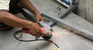 WORKER CUTTING STEEL WITH ELECTRIC WHEEL GRINDER Stock Image