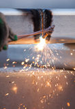 Worker cutting steel pipe using metal torch and install roadside Royalty Free Stock Photo