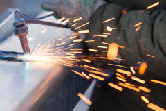Worker cutting steel pipe using metal torch and install roadside Stock Photo