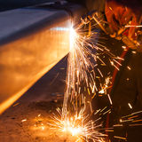 Worker cutting steel pipe using metal torch and install roadside Stock Image