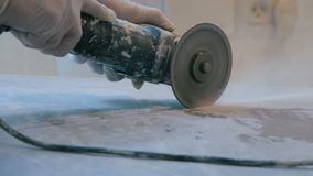 Worker cutting a tile using an angle grinder at construction site stock video