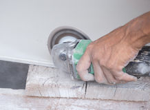 Worker cutting a tile using an angle grinder Stock Photos