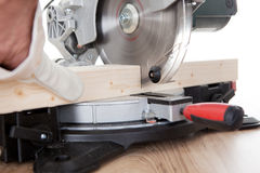 Worker cutting timber using circular saw Stock Image