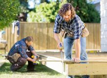 Worker Cutting Wood With Saw While Coworker Royalty Free Stock Photos