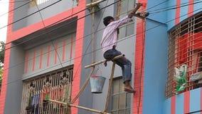 Worker on a dangerous bamboo scaffolding paints a building in Rajshahi, Bangladesh. RAJSHAHI, BANGLADESH - NOVEMBER 10, 2016: Worker on a dangerous bamboo stock video
