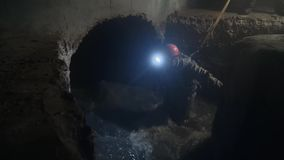 Worker in dark city sewage with large water flow.