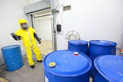 Worker dealing with toxic substance. Fully protected in yellow uniform, mask, and gloves professional dealing with barrels with toxic wastes stock photography