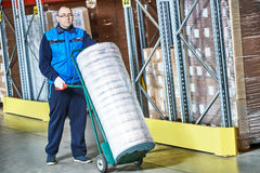 Worker with delivery cart in warehouse Stock Images