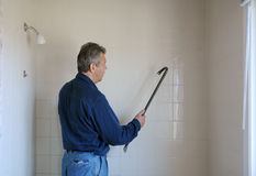 Worker demolishing a bathroom wall Stock Photos