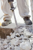 Worker demolishing the concrete with a jackhammer Stock Photos
