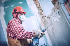Worker with demolition hammer breaking interior wall royalty free stock image